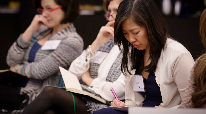 Women taking notes at an event